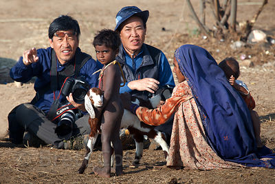 Japanese photographers take pictures of a poor woman and her child in Pushkar, Rajasthan, India. They took photos for 15 minu...
