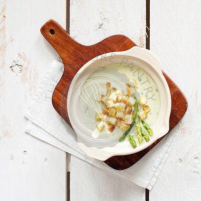 Asparagus soup cream with croutons on white wooden background