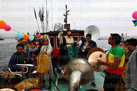 Brass band accompanying statue of St Peter on fishing boat during procession around port, St Peter and St Paul festival, Arica, Chile