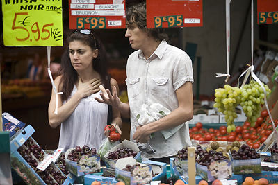 France - Paris - A young couple choose vegetables on a market stall on the Rue Mouffetard.