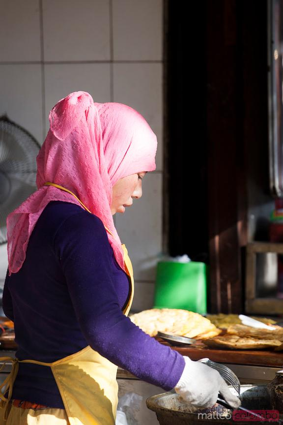 Young woman cooking in the muslim quarter of Xian, China