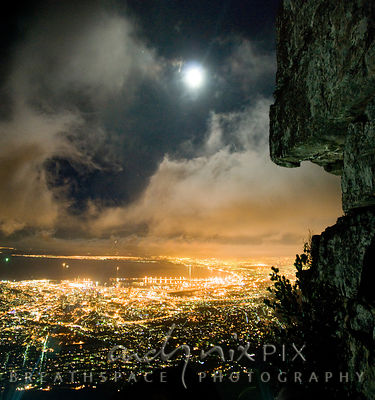 Moon shining through clouds over Cape Town city lights and Table Bay at night from mountain with cliff in foreground