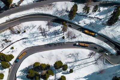 Timber trucks navigate the 10 sharp bends on the Maloja Pass in snowy weather