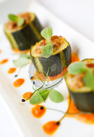 Starter of stuffed courgettes served with a butternut squash sauce.
