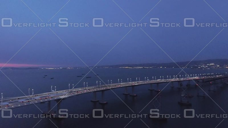 San Francisco Bay Bridge Aerial Pan Oakland to Treasure Island Evening Sky. California