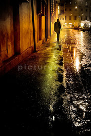 An atmospheric image of a lone woman walking down an empty, old street at night, lit by streetlights in Rome, Italy.