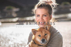 close up of caucasion dog mom holding shiba inu in her lap