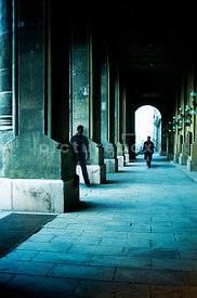 An atmospheric image of a man waiting to attack another man, walking towards him, down an empty walkway.