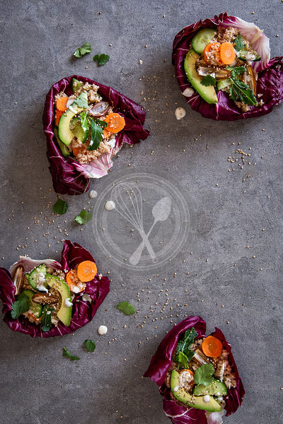 Radicchio bowls with couscous and vegetables over grey concrete background with copy space