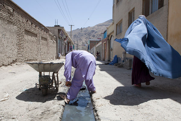 Bashir 13 ans nettoie le caniveau d'une rue commercante à Kaboul, Afghanistan / Bashir 13 years-old is cleaning the gutter of...