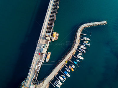 Various boats of different shapes and sizes moored at a curved pier in Port Kembla. NSW Australia