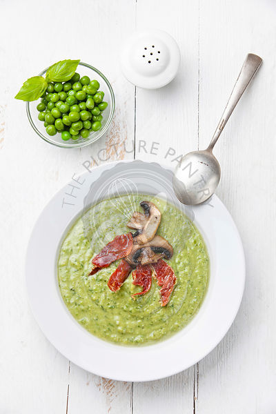Green pea soup in bowl on white wooden background