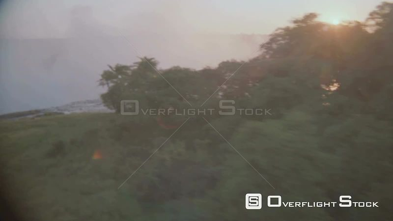 Aerial medium shot side view of riverbank behind thick vegetation to river flowing over lip, sun reflecting on mist in gorge ...