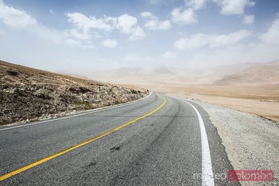 Deserted road through high mountains of central Asia
