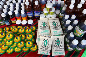 Cream for arthritis , bottles of various medicine and bags of coca leaf flour on stall at trade fair promoting alternative pr...