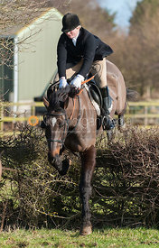 Louisa Fear jumping the first hedge