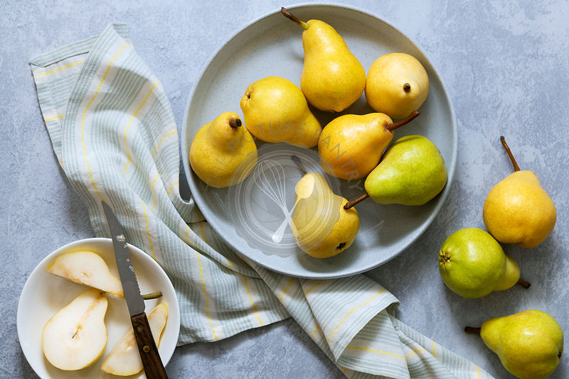 Whole pears with a sliced pear in a dish.