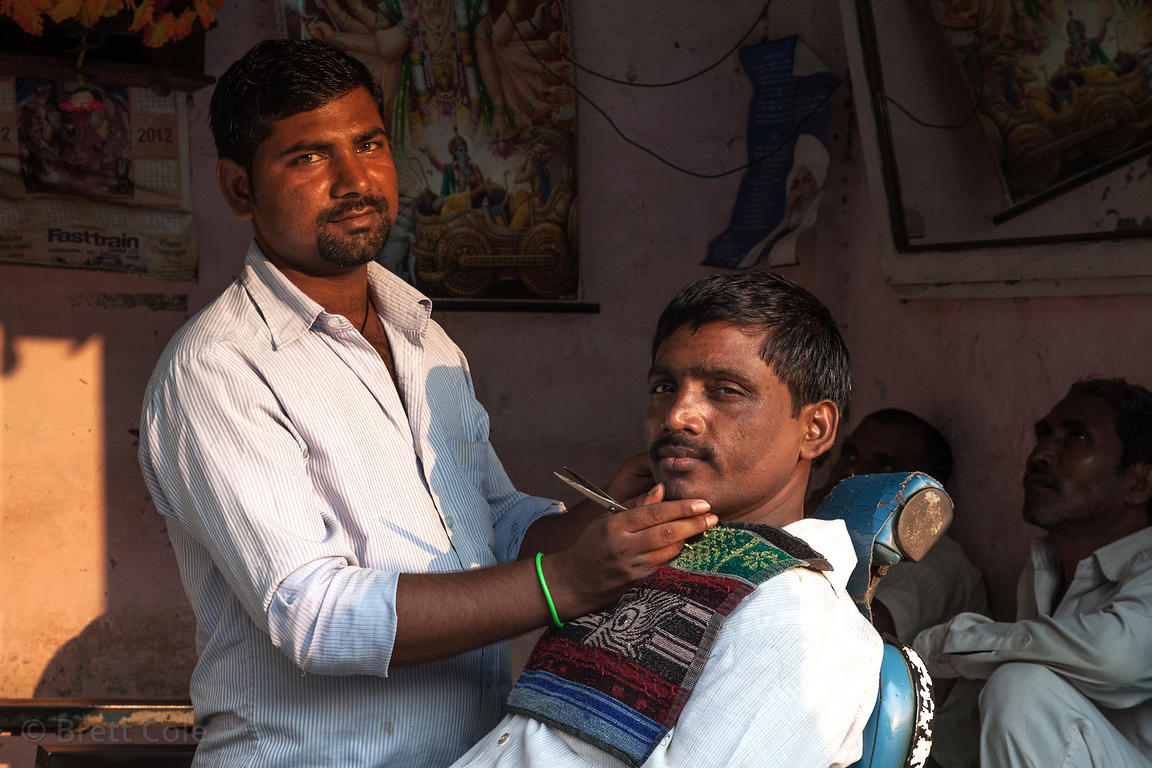 A barber gives a shave in the Kokri Agar slum, Mumbai, India.