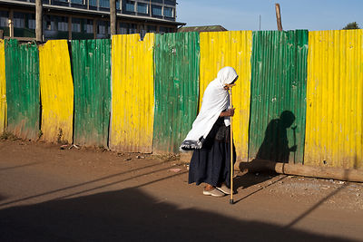 Ethiopia - Addis Ababa - A traditionally dressed woman walks with her stick past a yellow and green iron fence shielding a ne...