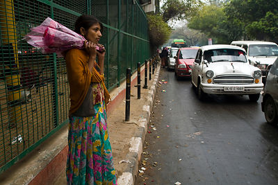 India - Delhi - Ram Pyari, 12 waits to sell flowers at a busy crossing