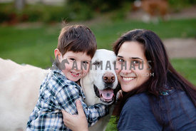 family-hugging-old-white-labrador-at-park