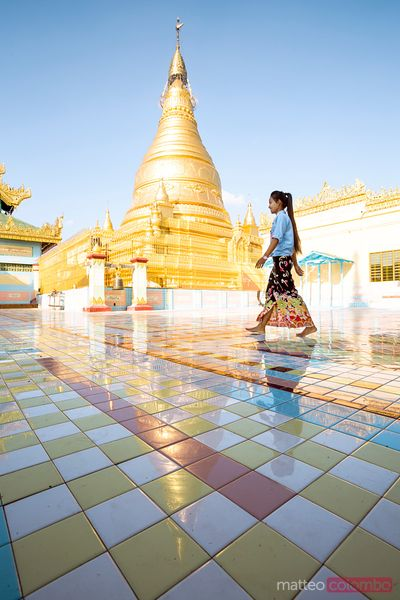 Burmese woman walking near golden pagoda, Myanmar