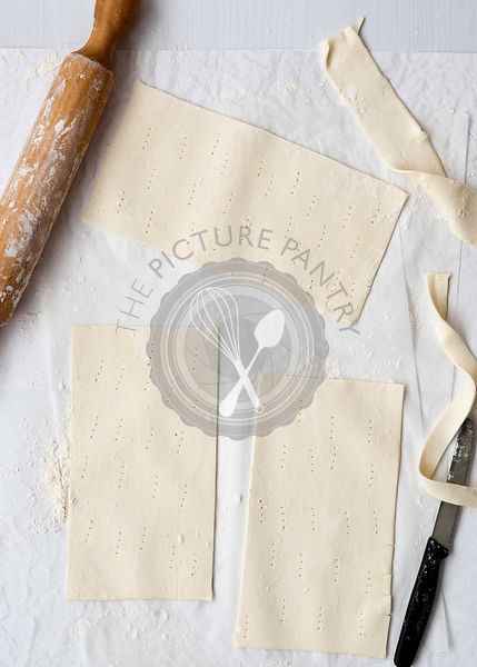 Three rectangular pieces of rolled pastry with a rolling pin and knife on baking paper.