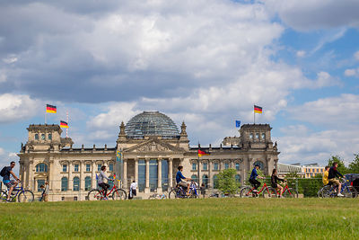 People Cycling past The Reichstag Building