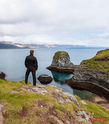Man looking at rugged coastline, Snaefellsnes peninsula, Iceland