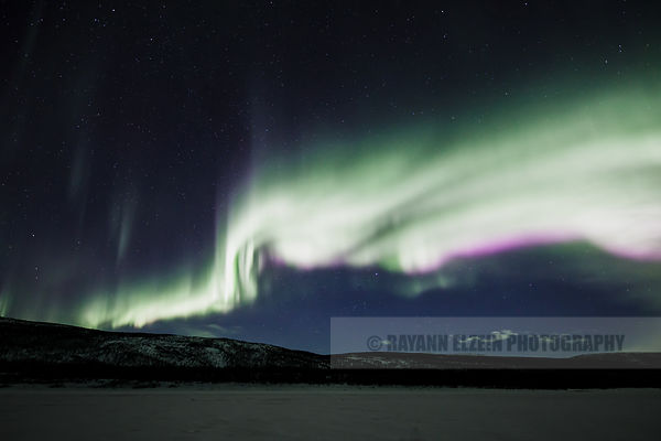 Aurora Borealis with purple nitrogen fringe above the Teno River in Utsjoki, Finnish Lapland