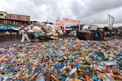 A pile of wrappers from plastic bottles sits next to a dumpster in the Dharavi slum, Mumbai, India.
