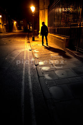 An atmospheric image of the silhouette of a mystery man, standing in a dark street at night.