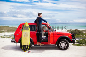 Surfer and dog at the beach in red jeep with surfboard.