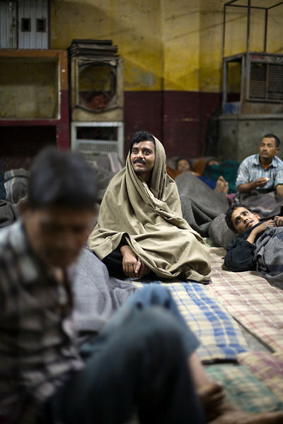 India - Delhi - Homeless men watch television in the Fatepuri night shelter for the homeless