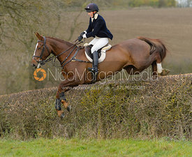 Katie Barber jumping a hedge on Graham Smith's
