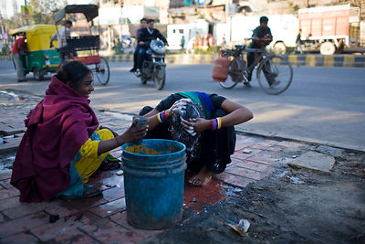India - Delhi - A homeless woman washes her hair by the side of the road