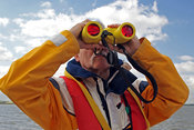 Man in sailing waterproofs looking through binoculars
