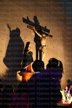 Man holding daughter in front of crucifix inside Las Nazarenas church, Lima, Peru