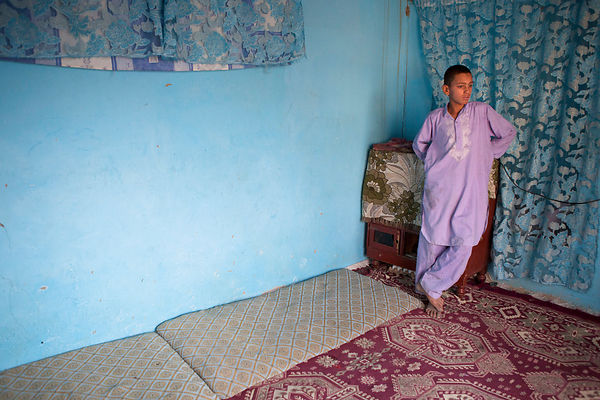 Bashir, 13 ans, debout dans la pièce prété par son oncle, Kaboul, Afghanistan / Bashir, 13, standing in the room worshiped by...