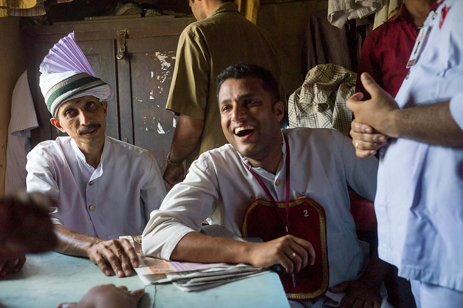 Waiters laugh and joke during a break in the staffroom of the Indian Coffee House, Kottayam