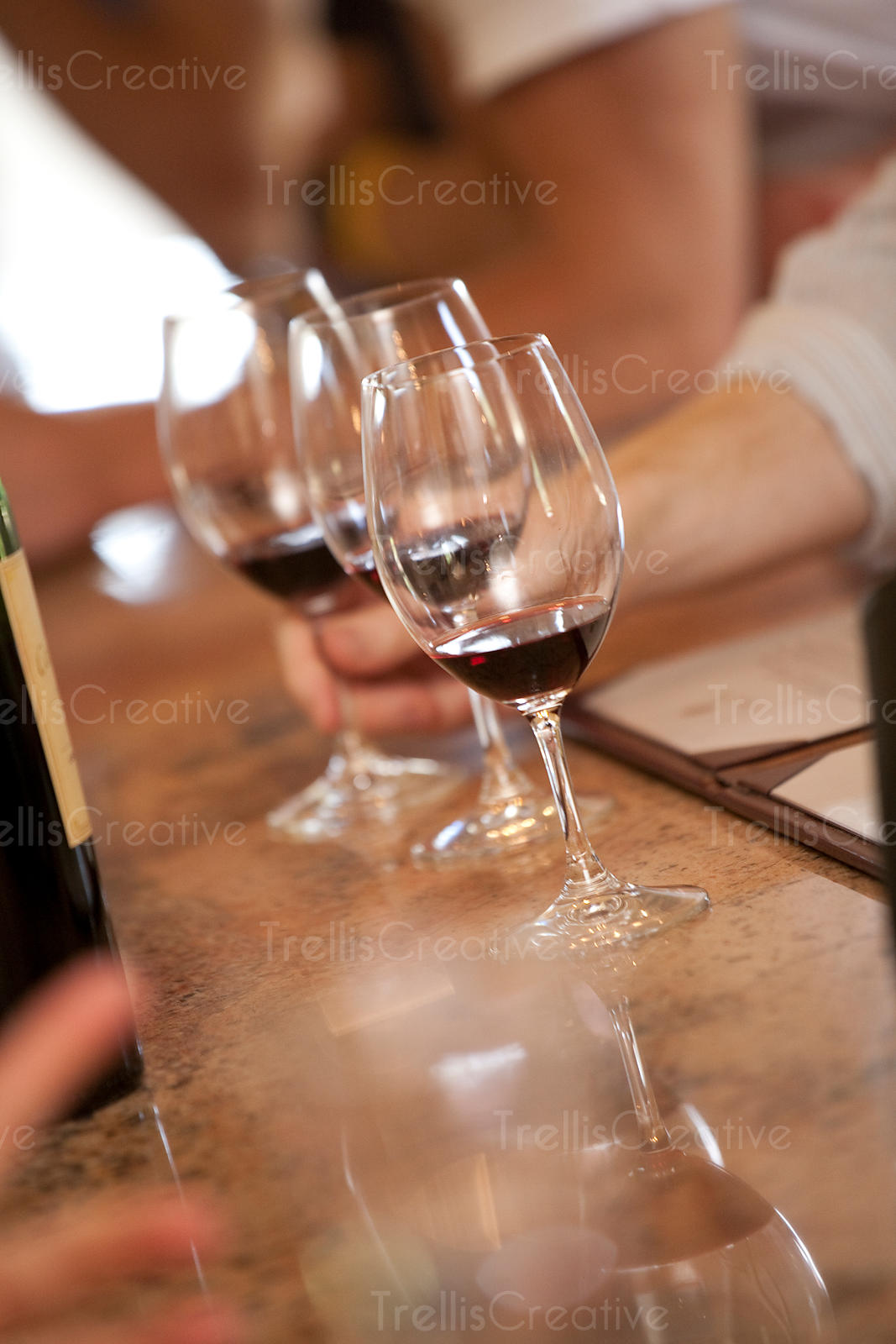 A man reaches for a glass of red wine at a winery tasting room