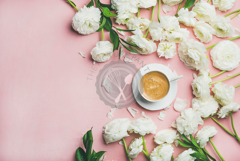 Flat-lay of cup of coffee surrounded with white ranunculus flowers over light pink background