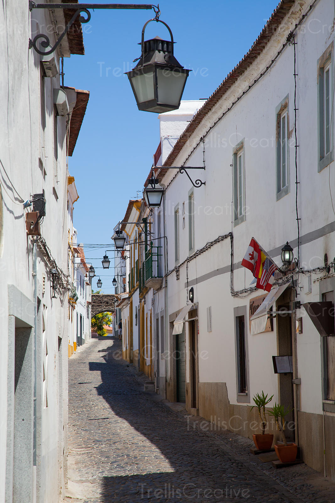 Narrow street in Evora, Portugal lined with old lanterns