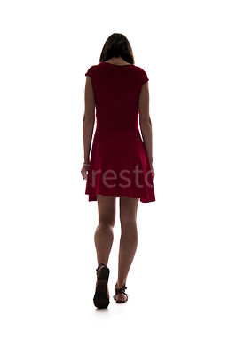 A semi-silhouette of a woman in a red dress walking away – shot from low level.