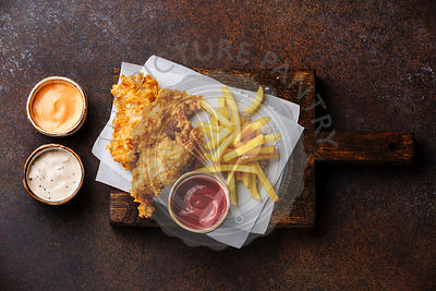 Fish and Chips british fast food with three popular sauce for choice on brown background
