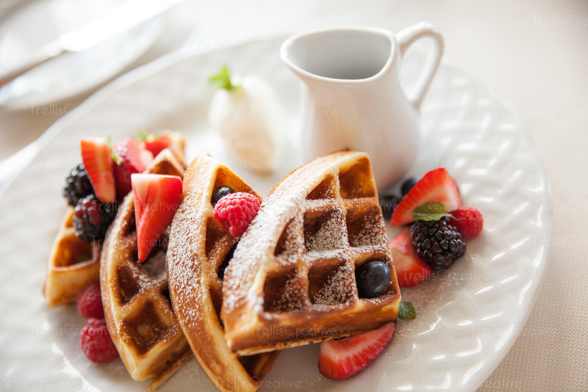 Close-up of waffles and berries with maple syrup in a jar