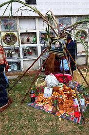 Sugar cane shrine with bread offerings for deceased policeman in cemetery, Todos Santos festival, La Paz, Bolivia