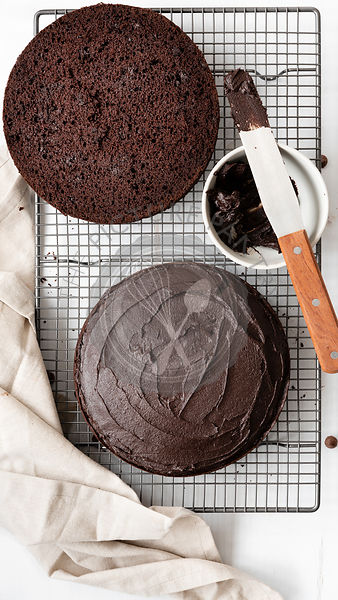 Round chocolate cake cut in halves with one half covered in chocolate icing.