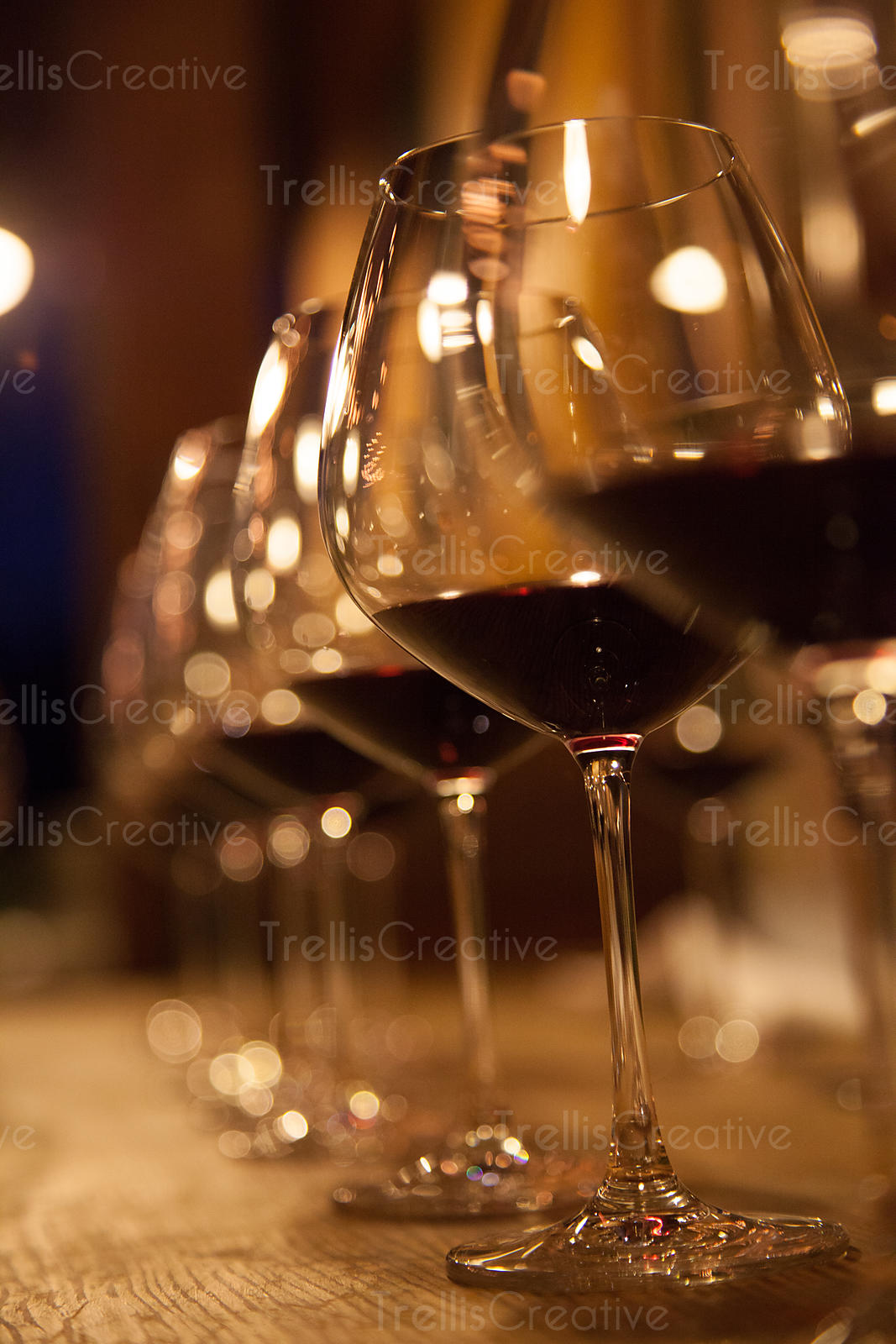 A neat row of wine glasses with red wine.