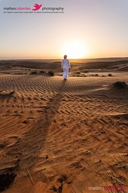 Arabic man with typical dress watching sunrise in desert, Oman